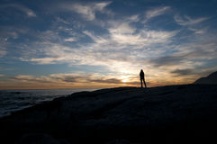 Solitude Sunset. Girl alone watches sunset at Noordhoek near Cape Town Stock Image