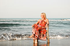 Solitude woman on the beach. Young woman sitting on an old chair by the sea Stock Photos
