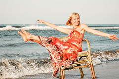 Solitude woman on the beach. Young woman sitting on an old chair by the sea Royalty Free Stock Images