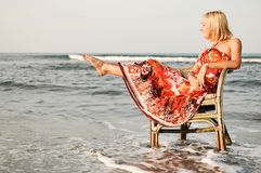 Solitude woman on the beach. Young woman sitting on an old chair by the sea Stock Image