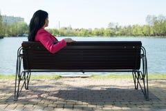 Solitude woman on bench in park. Solitude- Sad woman sitting on bench in park looking to the water Stock Photos