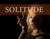 Solitude written on virtual screen. hand of young woman melancholy and sad at the window in the rain. Solitude written on virtual screen. hand of young woman Stock Photography