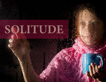 Solitude written on virtual screen. young woman melancholy and sad at the window in the rain, she holding a cup of hot. Coffee or tea Stock Image