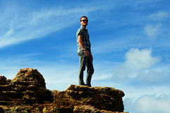 Solitude-Young man alone on mountain top Royalty Free Stock Image