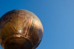 Soljordklot som framme göras av metall av en blå himmel royaltyfri foto