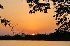 Sollöneförhöjningar över den orange kulöra sjön Arkivfoto
