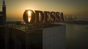 Sollöneförhöjningar bak stora Odessa Sign Ukraine royaltyfria foton