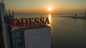 Sollöneförhöjningar bak stora Odessa Sign Ukraine royaltyfria bilder