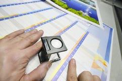 Solleciti la gestione di colore - stampi il controllo della lente di ingrandimento di produzione Fotografie Stock