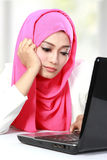 Solleciti la giovane bella donna asiatica che per mezzo di un computer portatile Immagini Stock