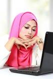 Solleciti la giovane bella donna asiatica che per mezzo di un computer portatile Fotografia Stock