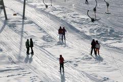 Sollevamento di sci della barra di T che tira sciatore sul pendio Immagine Stock