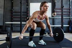 Sollevamento pesi motivato della donna in palestra Immagini Stock