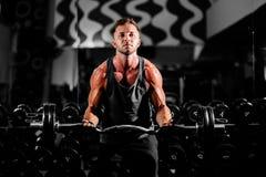 Sollevamento pesi motivato muscolare bello di allenamento dell'uomo in palestra Fotografie Stock Libere da Diritti