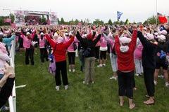 Sollevando le mani alla camminata di Avon per cancro della mammella Fotografie Stock Libere da Diritti