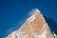 Solljus överst av det Masherbrum bergmaximumet i en morgon, Goro I Royaltyfri Bild