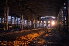 Solljus av solnedgången i stor övergiven industribyggnad av den Voronezh grävskopafabriken Royaltyfri Fotografi