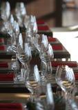 Solljus exponerar en trätabell mycket av tomma exponeringsglas och vitstearinljus Arkivbild