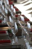 Solljus exponerar en trätabell mycket av tomma exponeringsglas och vitstearinljus Arkivfoto