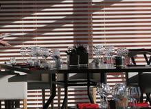 Solljus exponerar en trätabell mycket av tomma exponeringsglas och vitstearinljus Arkivbilder