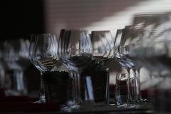 Solljus exponerar en trätabell mycket av tomma exponeringsglas och vitstearinljus Fotografering för Bildbyråer