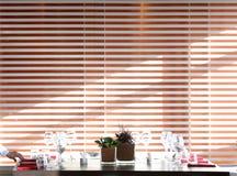 Solljus exponerar en trätabell mycket av tomma exponeringsglas och vitstearinljus Arkivfoton
