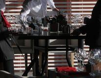 Solljus exponerar en trätabell mycket av tomma exponeringsglas och vitstearinljus Royaltyfria Foton