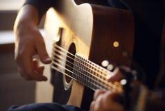 Solljus exponerar gitarristen som spelar en melodi på en gitarr arkivfoton