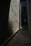 Solljus på byggnad i gränd Arkivfoto