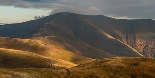 Solljus på kullar Arkivbild