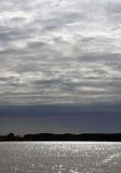Solljus på yttersidan av sjön Att glo himmelmolnen Royaltyfria Bilder