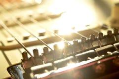 Solljus reflekterat av kroppen av en gitarr, bron är i förgrunden arkivbild