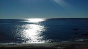 Solljus som blänker på havet Arkivfoton