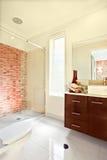 Solljus som fördelar inom av en modern badrumvägg och flooen arkivbilder