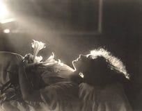 Solljus som faller på kvinnan med blommor som sover i säng royaltyfria foton