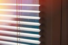 Solljus som kommer till och med persienner förbi fönstret Arkivbild