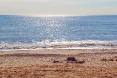 Solljus som reflekterar på att moussera det blåa havet på den Southwold stranden i UK royaltyfria bilder