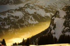 Solljus som reflekterar till och med dalmist i bergen Arkivbild