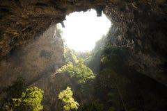 Solljus till och med ett grottahål i Thailand royaltyfria bilder