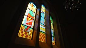Solljus till och med kyrkligt Fläck-exponeringsglas fönster arkivfilmer