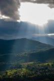 Solljus till och med moln Arkivbild