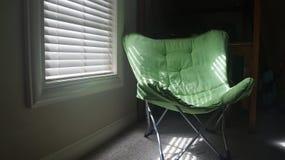 Solljus till och med rullgardiner på grön stol royaltyfria bilder