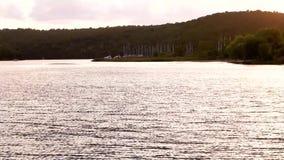 Solljusreflexion i vatten med port i bakgrundsSkradin port under solnedgång stock video