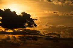 Solnederlag bak moln på solnedgången Arkivfoton
