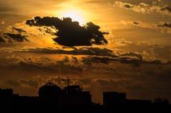 Solnederlag bak moln på solnedgången ovanför byggnader Arkivbild