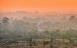 Solnedgång över asiatisk stad och djungel Arkivbilder