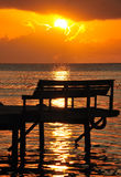 Solnedgång över bänk på pir Arkivfoton