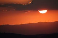 Solnedgång över berg med moderna väderkvarnar Arkivfoto