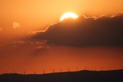 Solnedgång över berg med moderna väderkvarnar Royaltyfri Bild