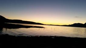 Solnedgång över berg och havet Arkivbilder